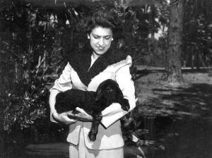 Mrs Bill Davis wearing pelts of Karakul fur & holding a lamb